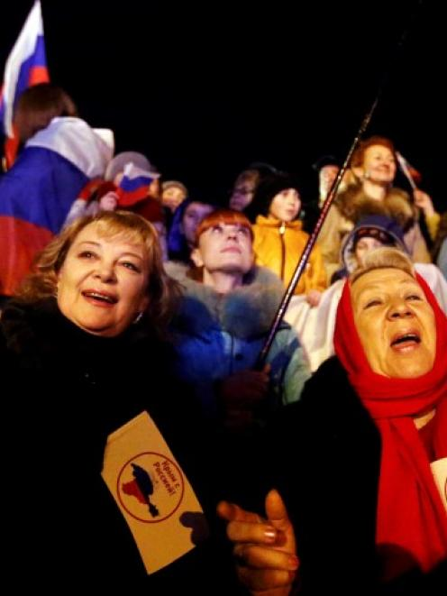 Two women hold flags reading 'Crimea is with Russia' as people wait for the announcement of...