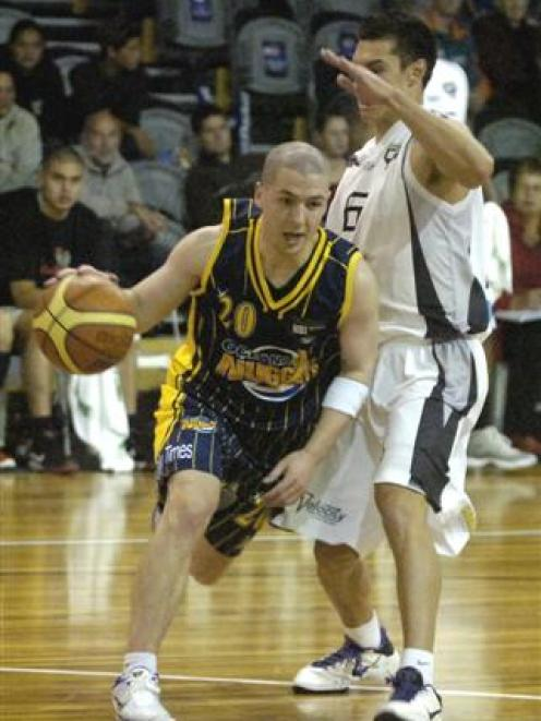 uggets point guard Scott O'Gallagher (left) drives past Hawks captain Jarrod Kenny during their...