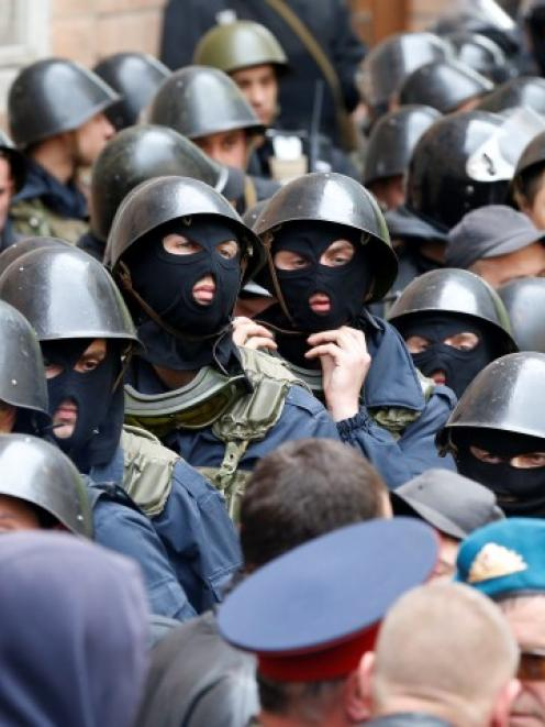 Ukrainian Interior Ministry security forces, blocked by pro-Russian activists, gather outside the...