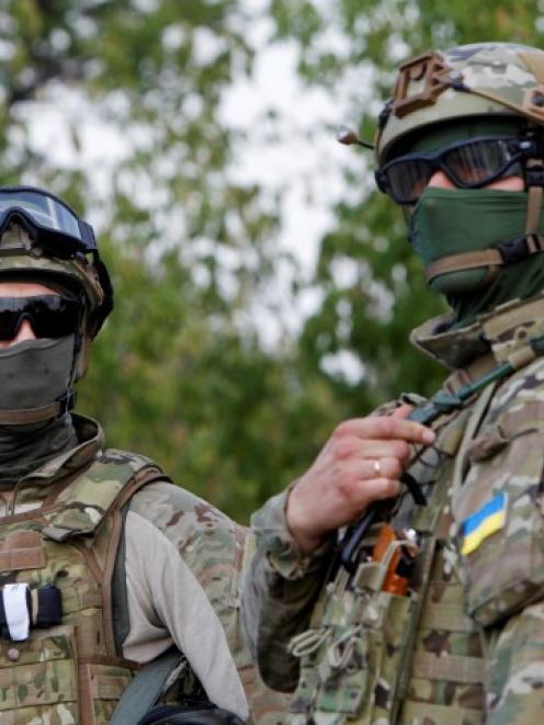Ukrainian servicemen guard a checkpoint near the eastern Ukrainian town of Debaltseve. REUTERS...