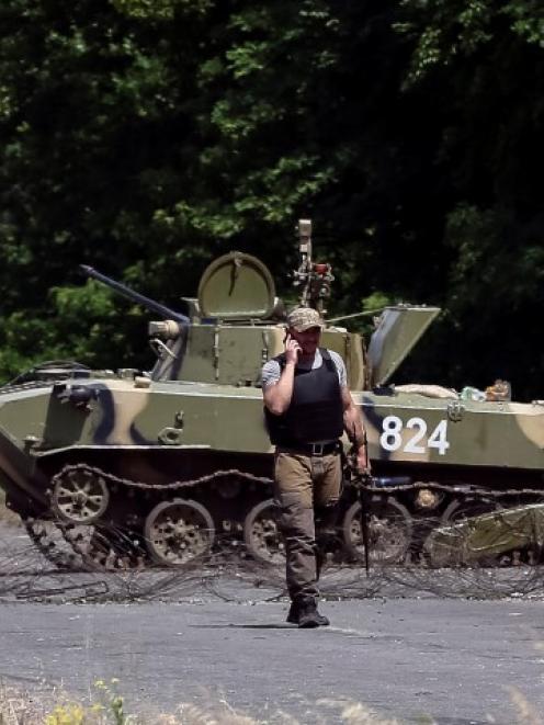 Ukrainian servicemen patrol at a checkpoint outside the eastern Ukrainian town of Slaviansk....