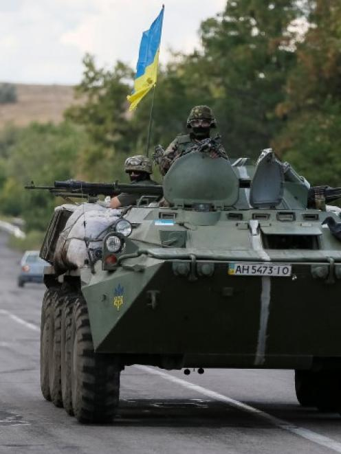 Ukrainian servicemen ride in an armoured vehicle near Debaltseve, Donetsk region. REUTERS/Gleb...