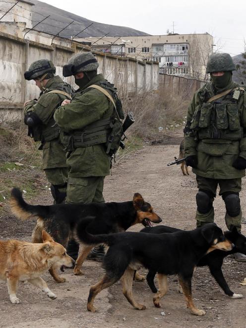 Uniformed men, believed to be Russian servicemen, near a Ukrainian military base in the village...