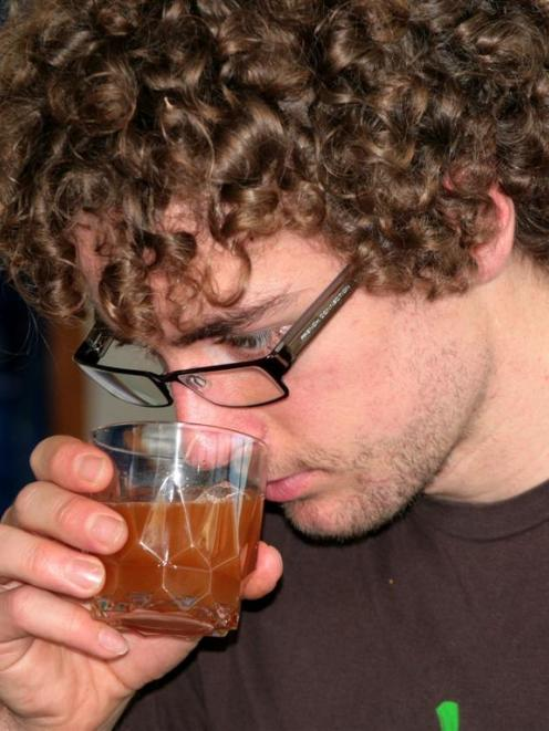University of Otago Brewers Association president Jaz Morris checks the progress of his latest...