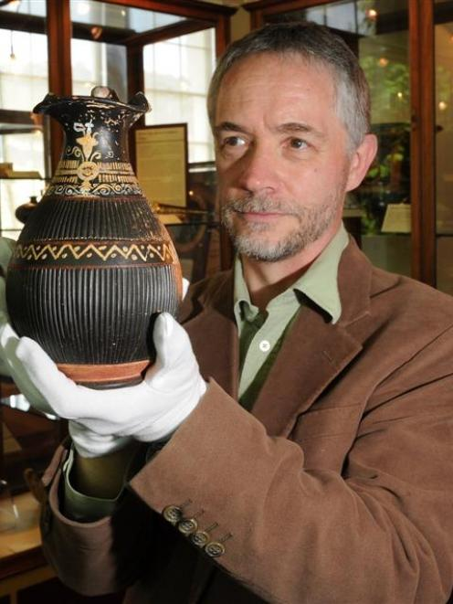 University of Otago Prof Robert Hannah takes a close look an ancient wine jar at the Otago Museum...