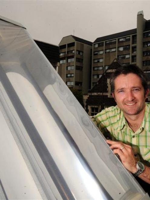 University of Otago researcher Andrew Wallace with his product created to provide free hot water...