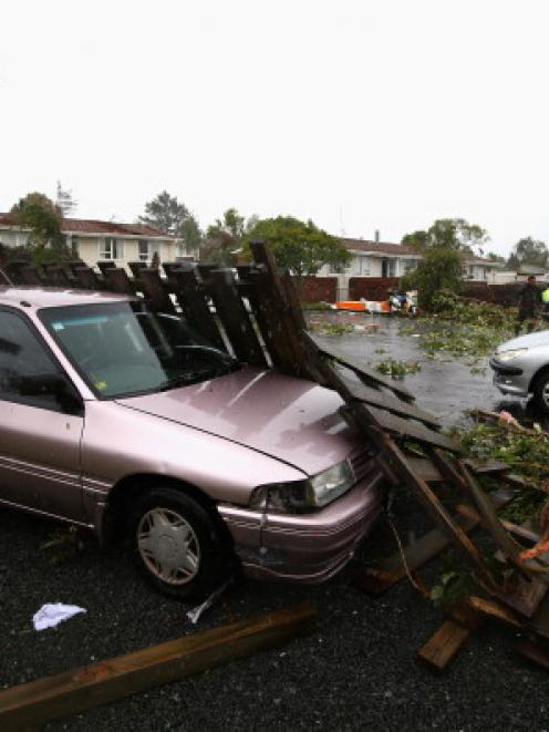 Uprooted trees and storm debris are scattered around the Auckland suburb of Hobsonville in the...