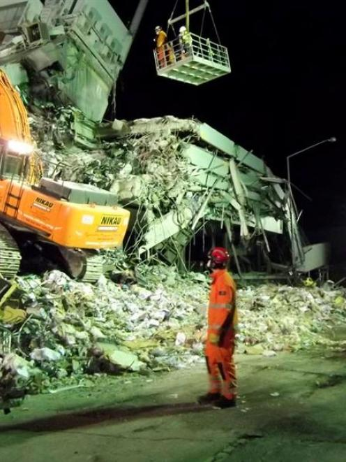 Urban Search and Rescue teams work through the night at the Pyne Gould Corporation building in...