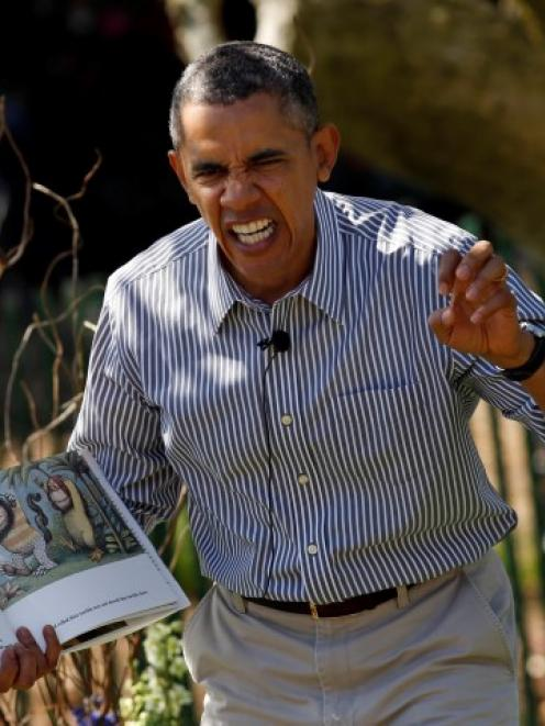 US President Barack Obama acts out a line while reading 'Where the Wild Things Are' during the...