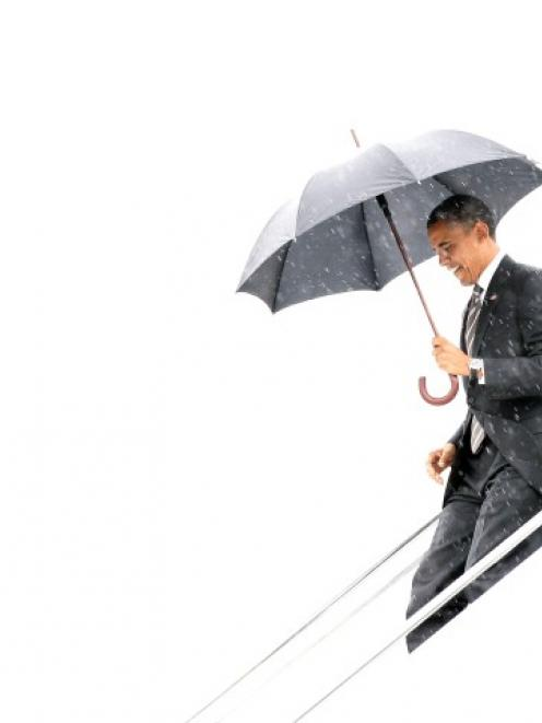 US President Barack Obama arrives under rainy skies in North Canton, Ohio, on his way to Kent...