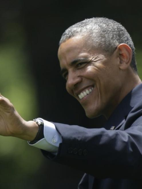 US President Barack Obama waves as he departs the White House on the South Lawn in Washington....