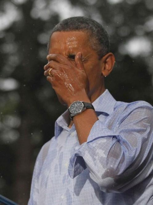 US President Barack Obama wipes rain off his face during heavy rainfall at a campaign rally in...