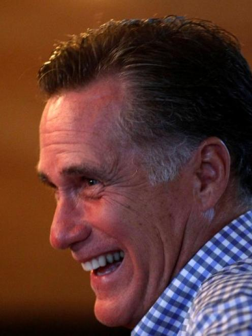 US Republican presidential nominee and former Massachusetts Governor Mitt Romney laughs as he...