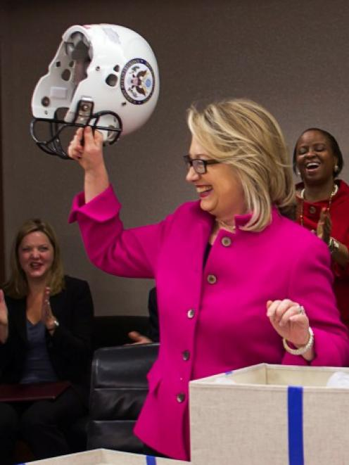 US Secretary of State Hillary Clinton holds up a football helmet with the State Department logo...
