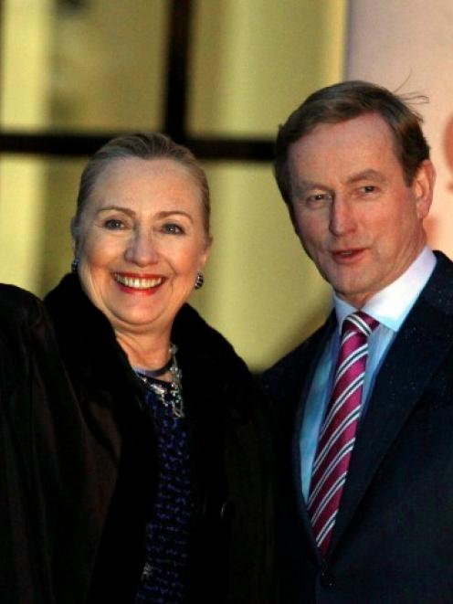 US Secretary of State Hillary Clinton is greeted by Irish Prime Minister Enda Kenny (R) as she...