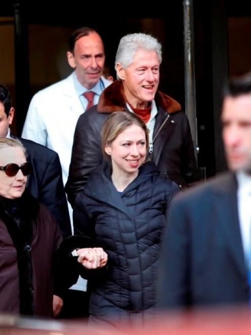 US Secretary of State Hillary Clinton (L) leaves New York Presbyterian Hospital with husband Bill...