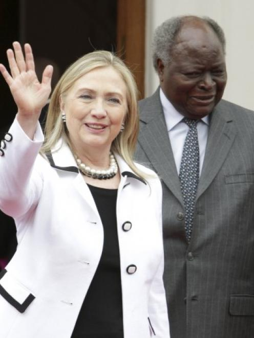 US Secretary of State Hillary Clinton waves after meeting with Kenya's President Mwai Kibaki at...