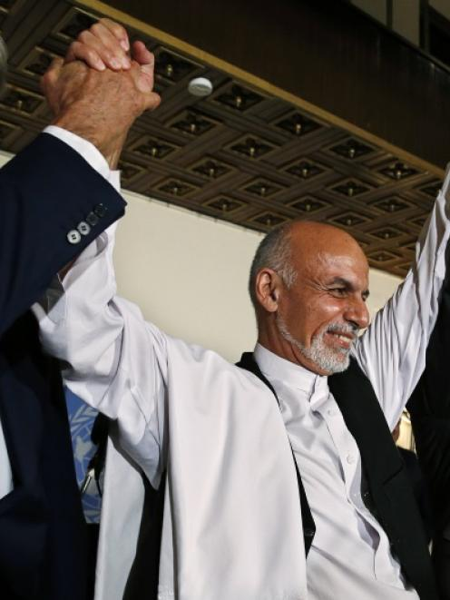 US Secretary of State John Kerry (L), Afghanistan's presidential candidates Ashraf Ghani (C) and...