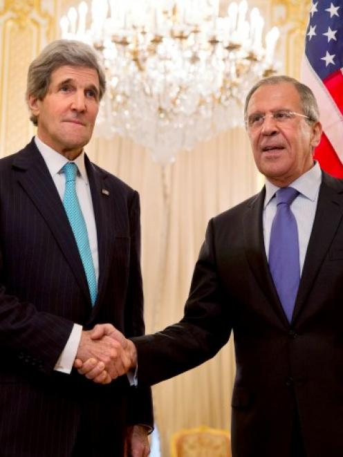 US Secretary of State John Kerry (L) shakes hands with Russian Foreign Minister Sergei Lavrov...