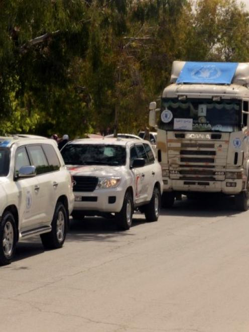 Vehicles carrying humanitarian supplies wait at a crossing point in Aleppo's Bustan al-Qasr....