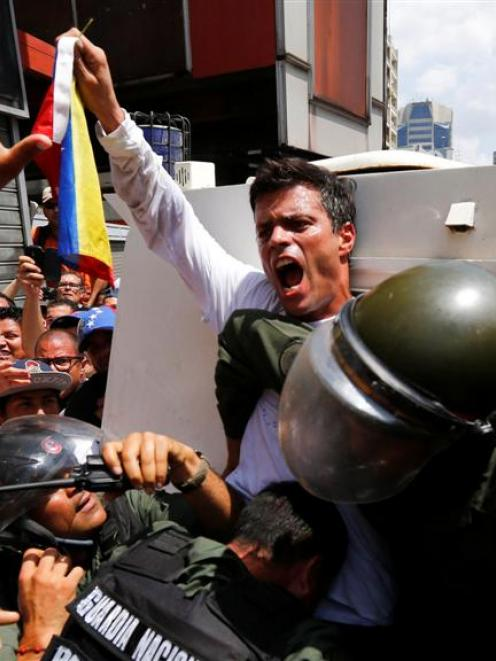 Venezuelan opposition leader Leopoldo Lopez gets into a National Guard armoured vehicle in...