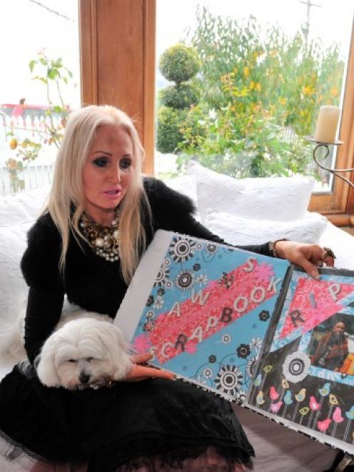 Victoria Davis, with her dog Panaish, looks through a scrapbook featuring her son, Jai Davis,...