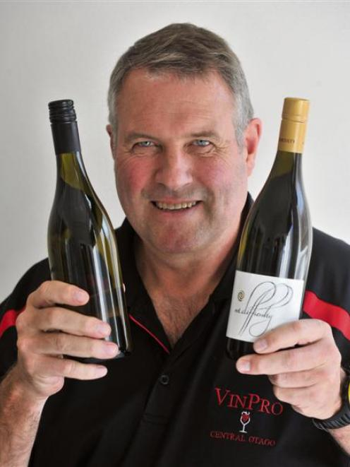 VinPro managing director Morley Hewitt holds a bottle with a standard screw cap (left) and one...