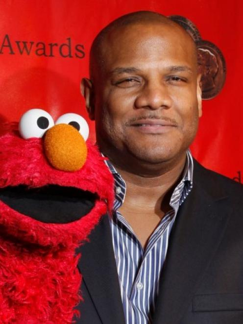 Voice actor Kevin Clash arrives with the puppet Elmo for the 2010 Peabody Award ceremony at the...