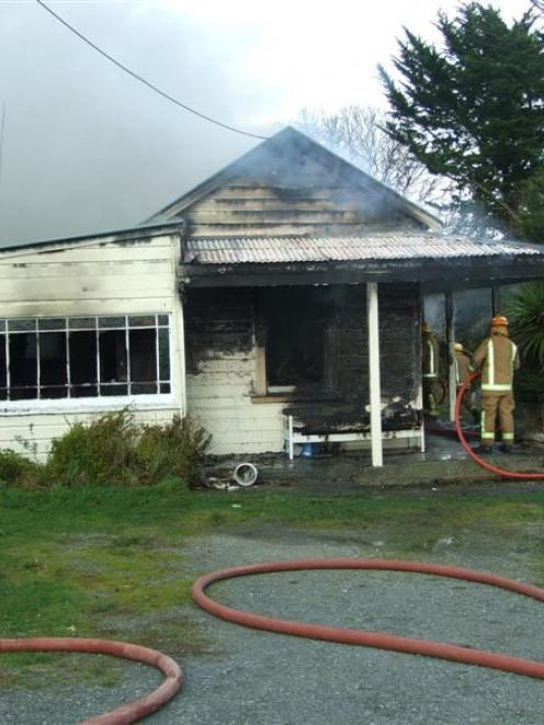Volunteer firefighters try to save this Kaitangata home yesterday  morning. Police and the Fire...
