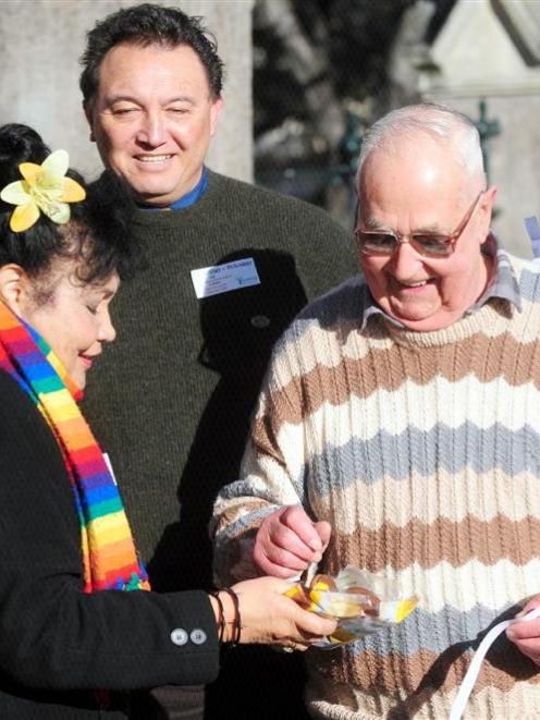 Volunteer Phil Rawson is given a biscuit by Selina Mulder, as First Church senior minister the...