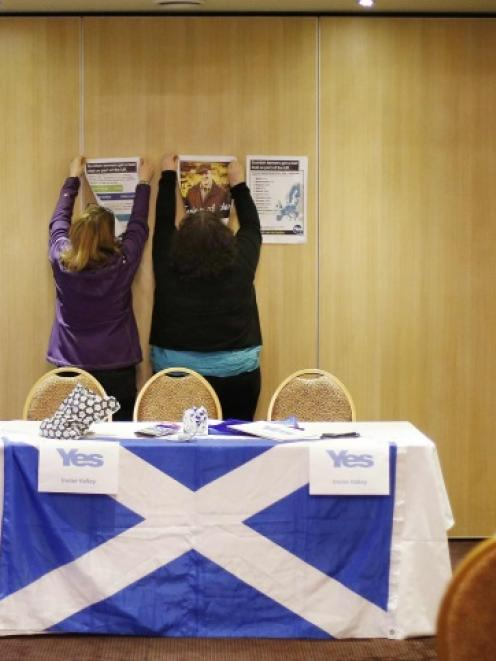 "Volunteers hang campaign signs before a ""Yes"" campaign meeting at the Fenwick Hotel in Kilmarnock..."