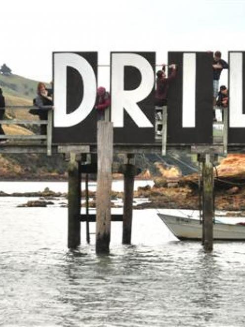 Volunteers remove letters from the ''No Drill'' sign on Quarantine Island's jetty in Otago...