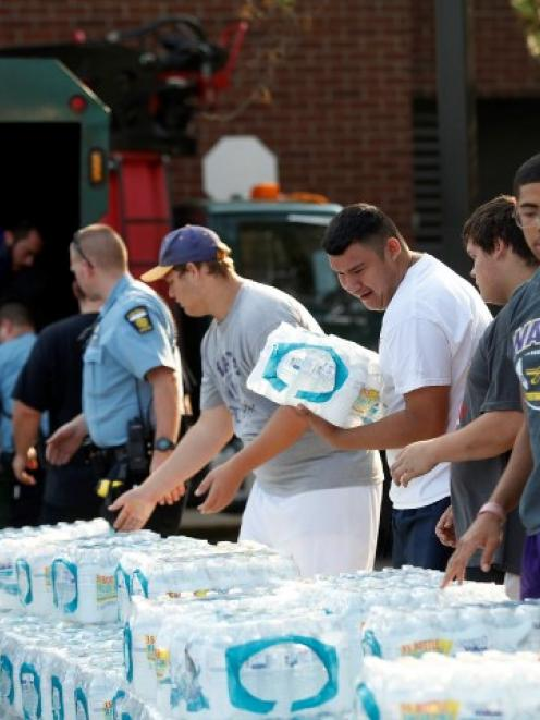 Volunteers unload drinking water from a truck outside Waite High School in Toledo, Ohio. REUTERS...