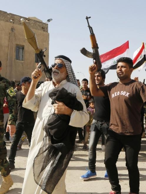 Volunteers, who have joined the Iraqi Army to fight against predominantly Sunni militants, carry...