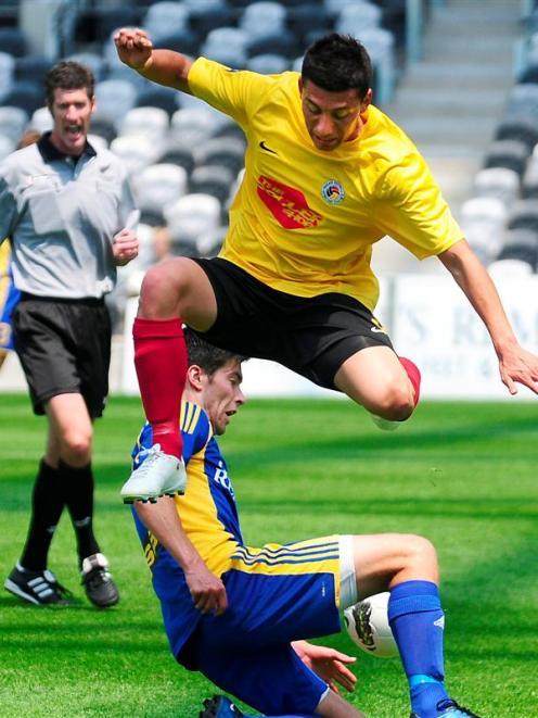 Waikato's Chilean striker Eder Franchini leaps over sliding Otago midfielder Sam Mepham as...