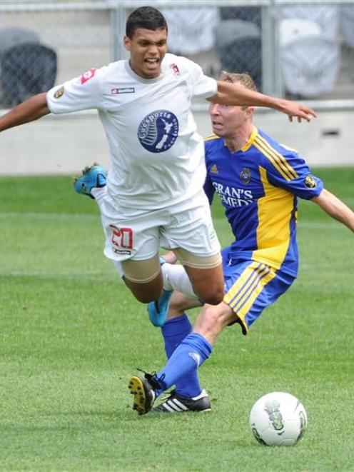 Waitakere United's Ryan de Vries is brought down in the tackle of Otago United's Craig Ferguson...