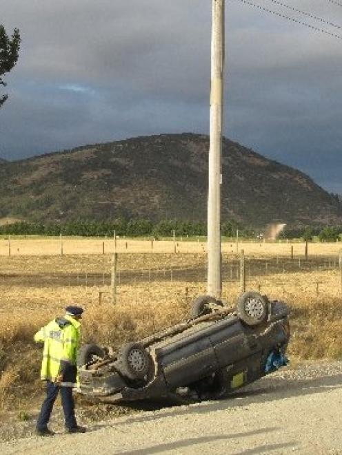 Wanaka constable Bruce McLean with an overturned car on the gravel section of Ballantyne Rd. Mt...
