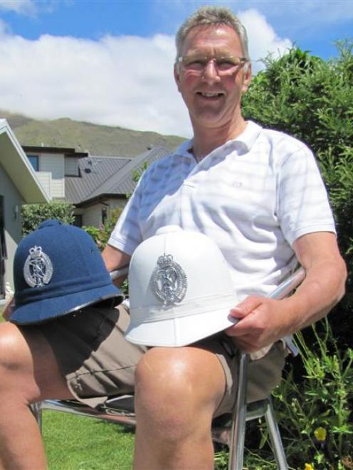 Wanaka detective Dave Evans with two of the helmets he once wore. Photo by Mark Price.