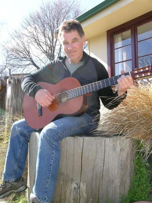 Wanaka musician Steve Brett at home with his classical guitar.  Photo by Marjorie Cook.