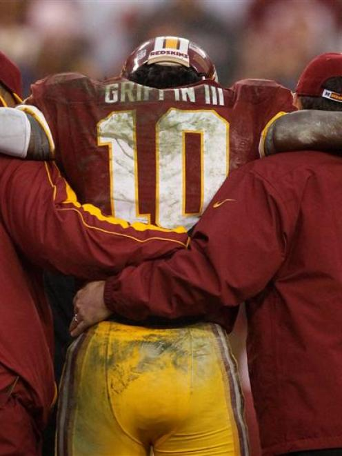Washington Redskins starting quarterback Robert Griffin III is helped off the field by team...