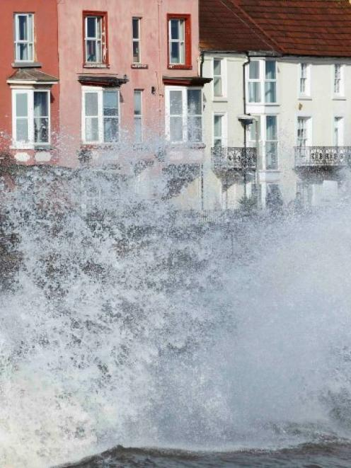 Waves crash against an already damaged railway line and buildings at Dawlish during storms in...
