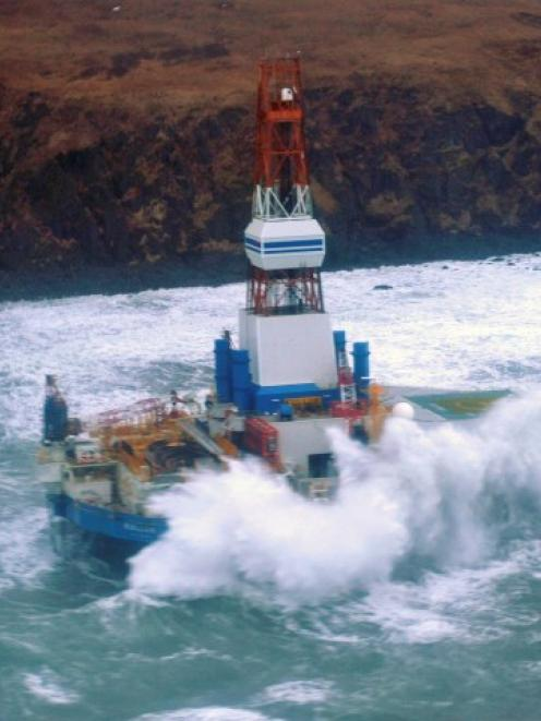 Waves crash over the conical drilling unit Kulluk where it sits aground on the southeast side of...