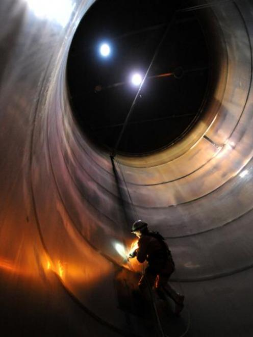 Welder Murray Ewing uses a grinder inside a milk silo at Fonterra's Edendale plant yesterday....
