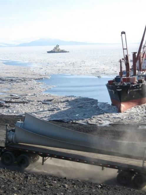 Wind turbine blades are transported by truck from McMurdo Station ice pier to the site where the...