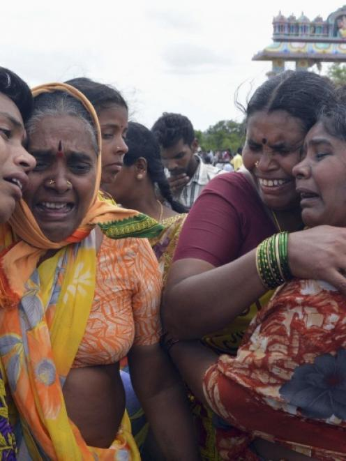 Woman cry at the site of a collision between a train and a school bus in Medak district in the...
