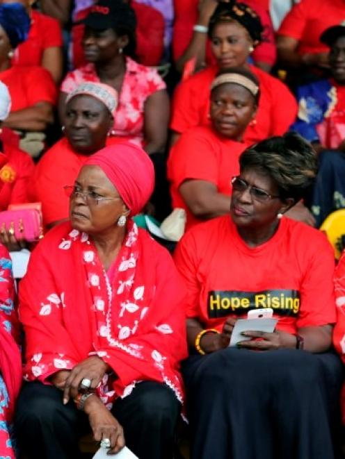 Women wearing red gather for a prayer vigil for the release of abducted secondary school girls in...