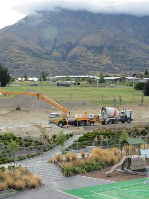 Work to add a pair of classrooms and turn vacant land into a playing field continued at...