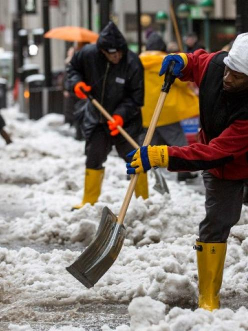 Workers clear snow in New York's financial district near Wall St. REUTERS/Brendan McDermid