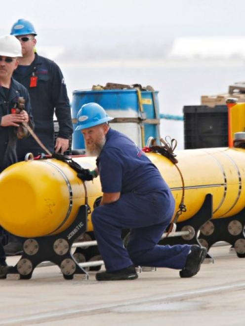 Workers help secure a Phoenix underwater mapping robot before it is loaded on to the Ocean Shield...
