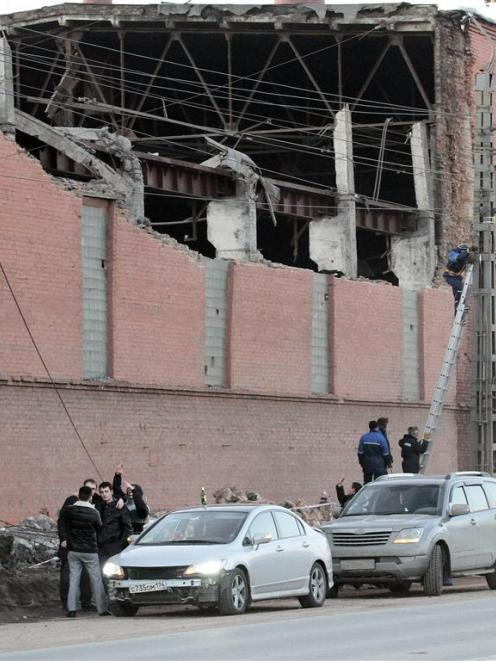 Workers repair damage caused after a meteorite passed above the Urals city of Chelyabinsk....